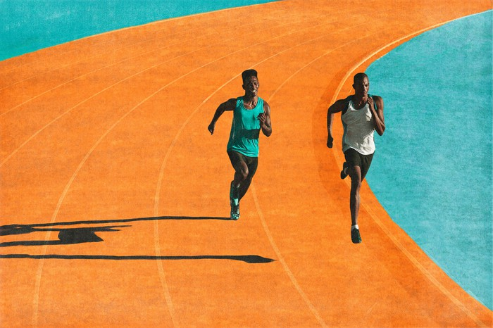Two people running on a bright orange track with a light blue border.