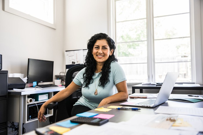 A woman sitting at her desk in her office, as if ready to help a client.