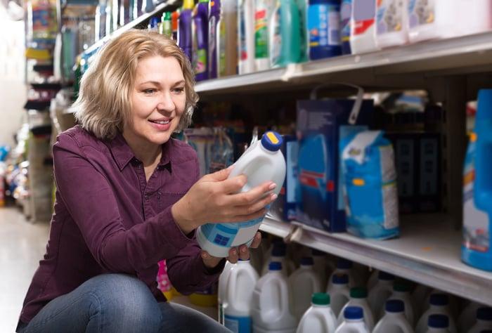Shopper à la bouteille d'eau de Javel en magasin