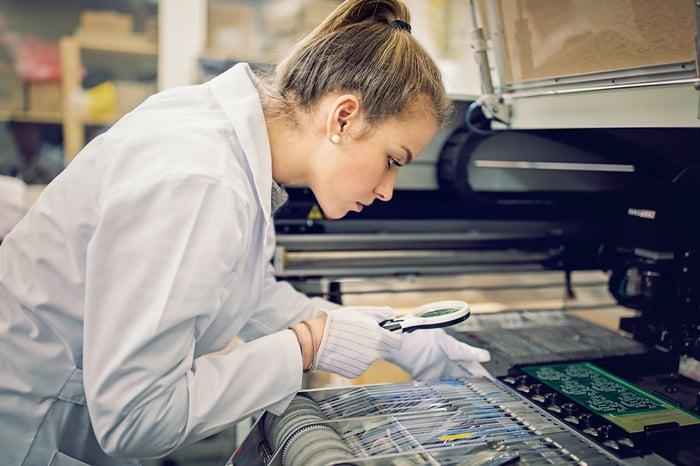 Technicien portant une blouse blanche tenant une loupe sur des puces semi-conductrices.