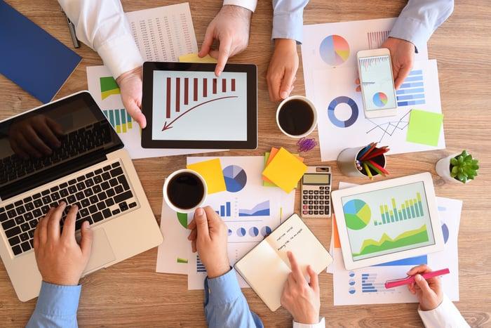 Un groupe d'investisseurs analysant des tableaux et des graphiques financiers.