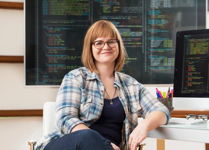 Personne assise dans un bureau devant un moniteur affichant le code logiciel.