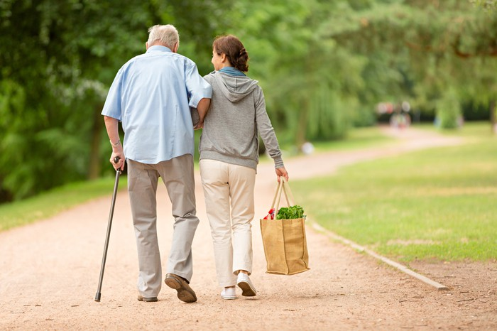 Woman helping elderly man.