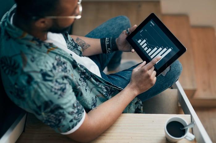 A man trades stocks on a tablet.