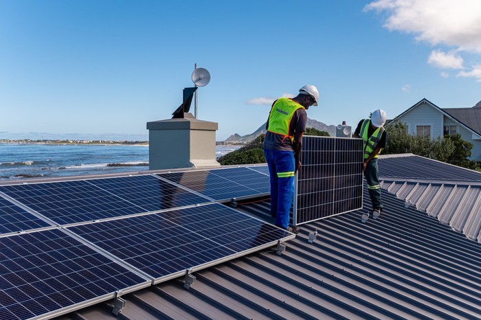 worker installing solar panels on roof with ocean in the background.