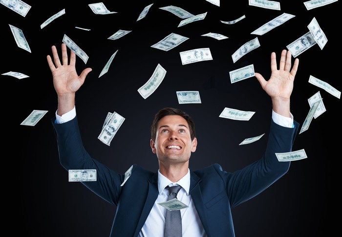 Person in suit throwing money into the air.