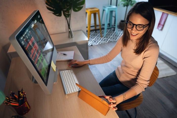Une femme est assise à un bureau sur lequel sont posés un clavier et un ordinateur.  Elle touche également l'écran d'une tablette