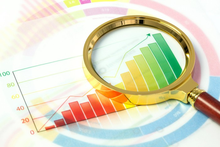 A magnifying glass lies on a colorful stock market data chart.