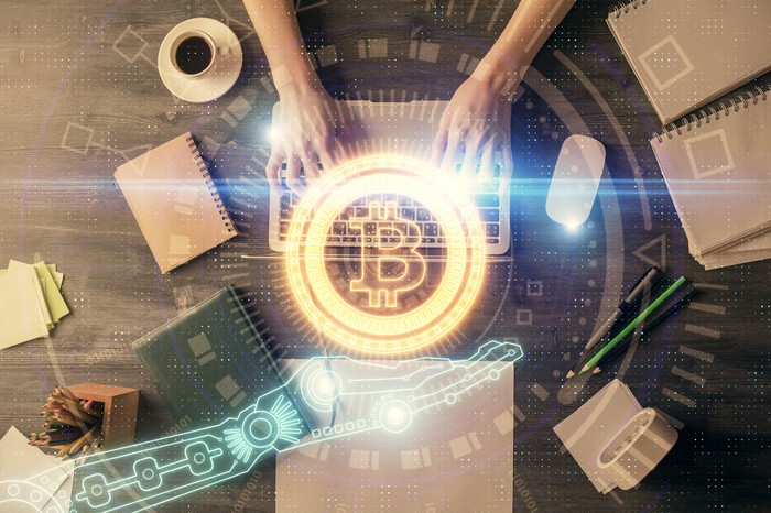 A Bitcoin hologram hovering above a laptop