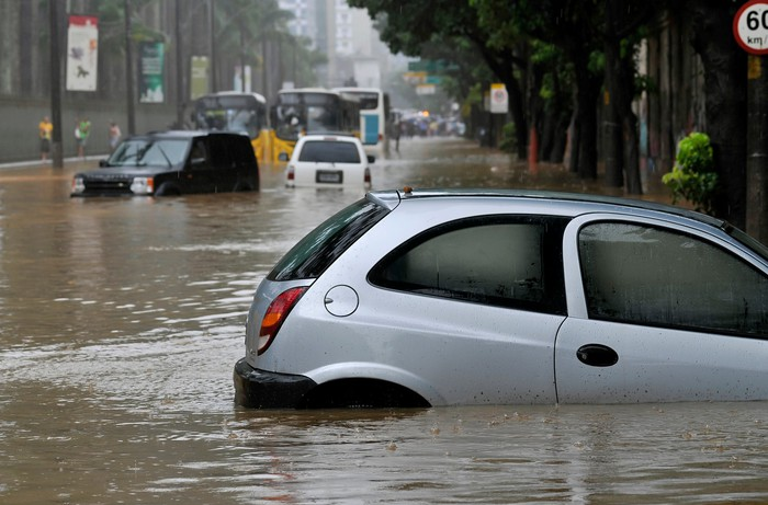 Several vehicles on a city road with high floodwaters.