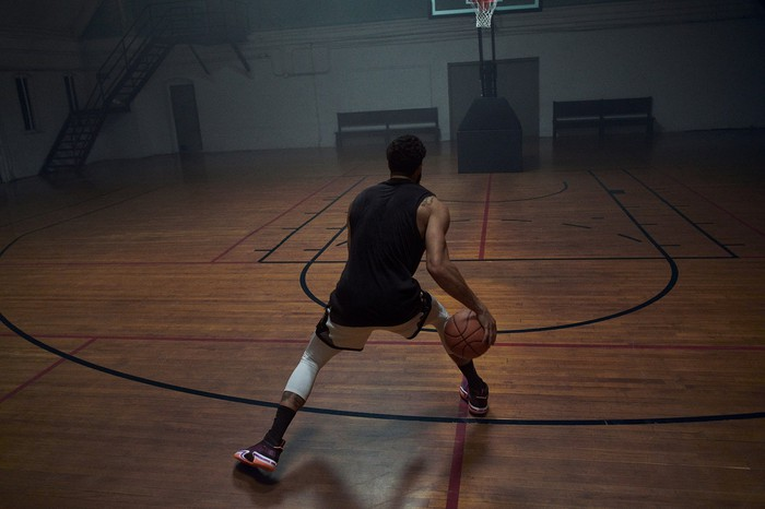 A basketball player with a ball on an indoor court.