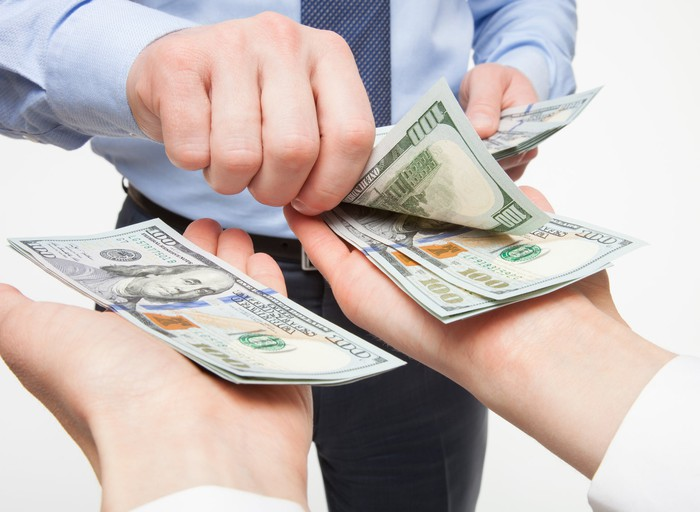 A businessperson's hand placing crisp one hundred dollar bills into two outstretched hands.
