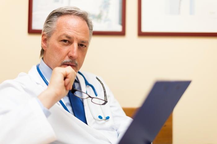 Un médecin tenant ses lunettes devant son visage alors qu'il réfléchissait profondément.