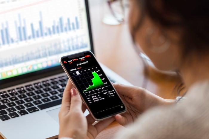 Un graphique boursier vert en hausse rapide affiché sur le smartphone d'une personne.