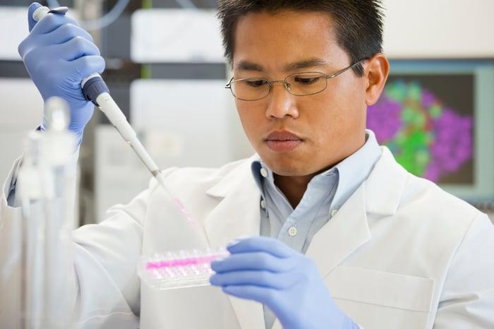 Un technicien de laboratoire utilisant une pipette pour placer du liquide dans une rangée de plateaux de test.