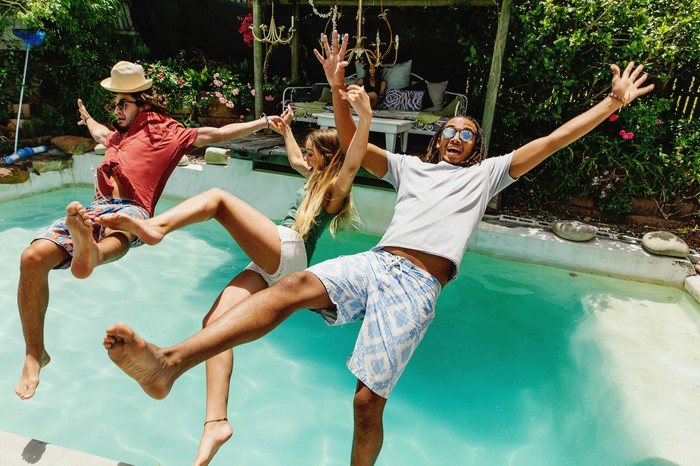 Three fully clothed people jumping backwards into a pool.