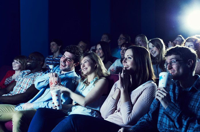 Folks smiling while watching something inside a theater.