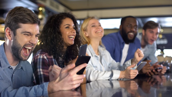 Five smiling people sitting at a bar with cell phones in hand.