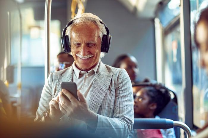 Personne portant des écouteurs regardant un smartphone dans un bus.