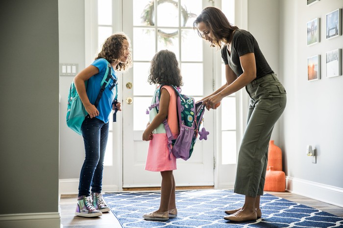 Mother packing daughter's backpack for school.