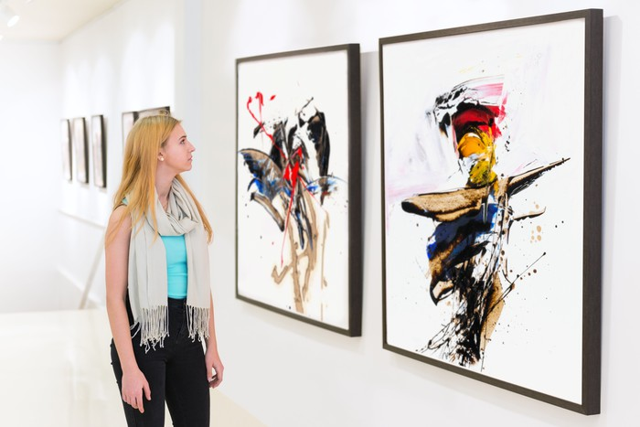 Someone in an art gallery looking at paintings.