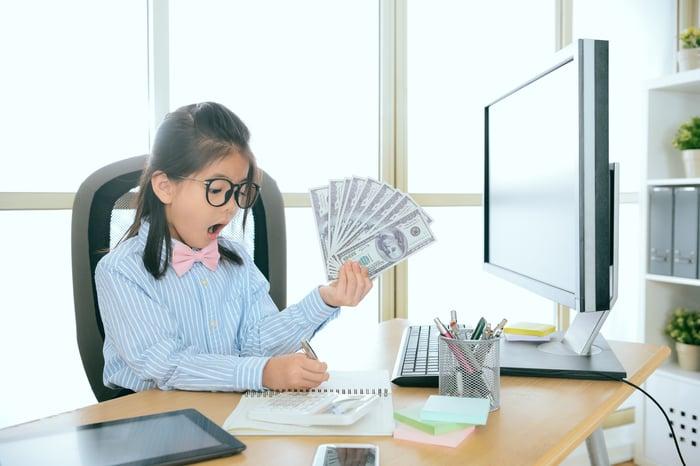Enfant au bureau devant un ordinateur, tenant beaucoup d'argent liquide.