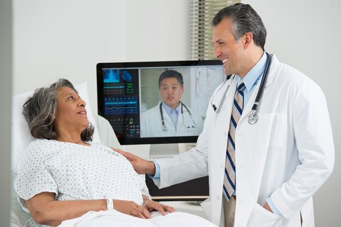 Un patient dans un lit d'hôpital parle à un médecin en personne et à un autre sur un écran.