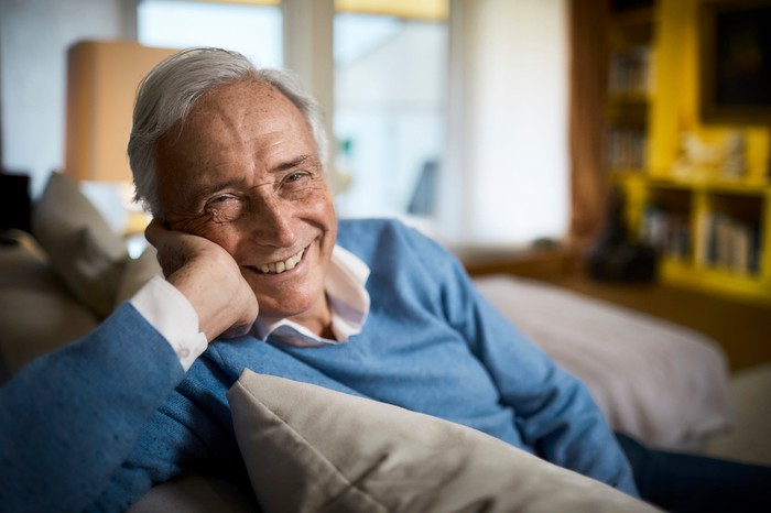 Retiree sitting on a couch and smiling.