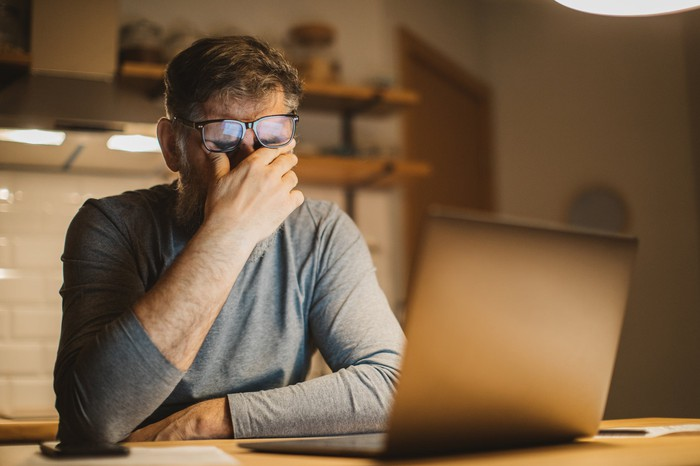 A visibly frustrated person rubs their eyes while sitting in front of a computer.