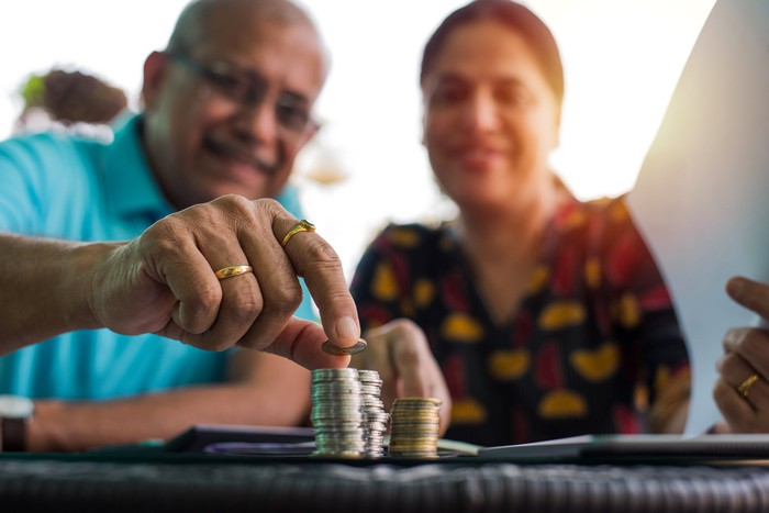 A couple sitting together while the man places a coin onto a pile.