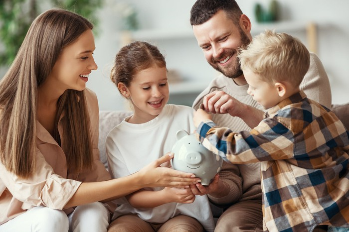 A family putting coins in a piggy bank.