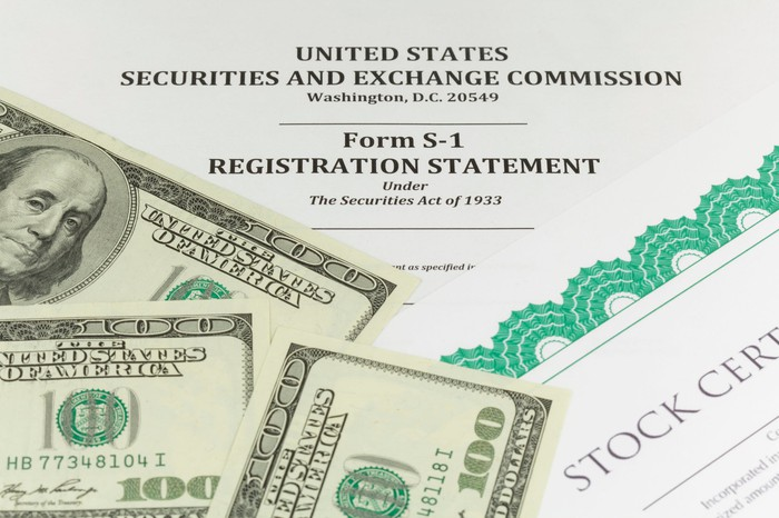 A paper S-1 registration statement form for an IPO, with a share certificate and several hundred dollar bills sitting on it.