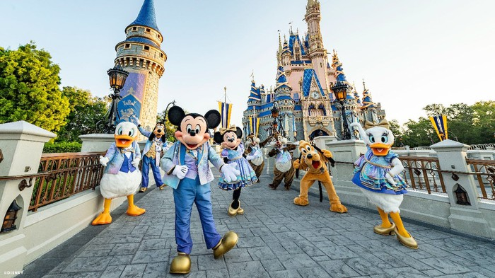 Mickey Mouse and his pals posing in front of the signature castle.