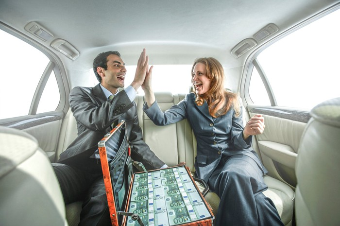 Man and woman high fiving in a car with a suitcase of cash on the seat.