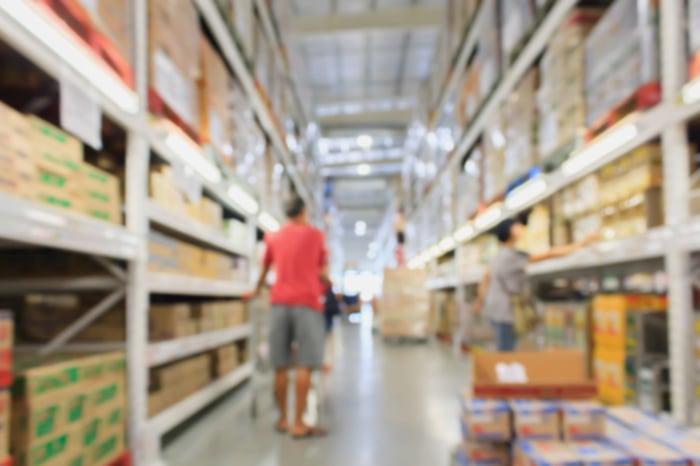 A shopper pushes a cart down an aisle between warehouse shelves of a warehouse shopping club store