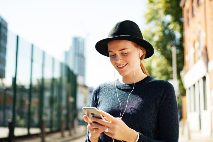 Une jeune femme écoutant de la musique sur son smartphone.