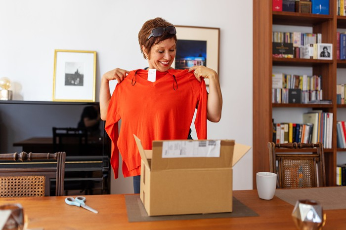 A consumer stands in her home surrounded by furniture holding up a piece of clothing she purchased online and had just removed from its shipping box, which sits on a table next to her