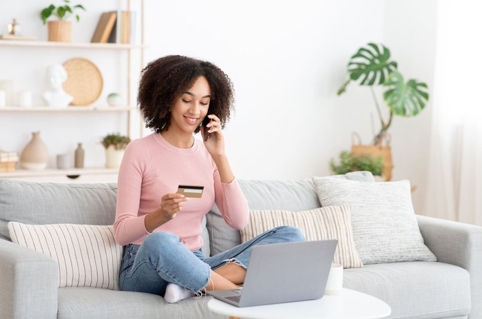 A person on their laptop and cell phone holding a credit card.