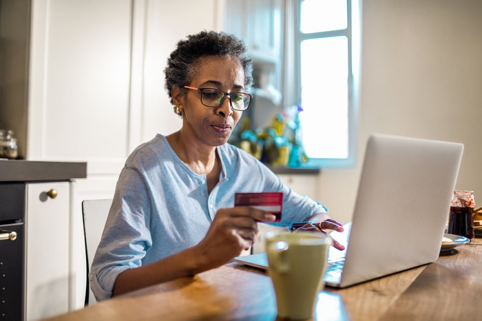 Mature person shops online while at home and holds a credit card in their hand.