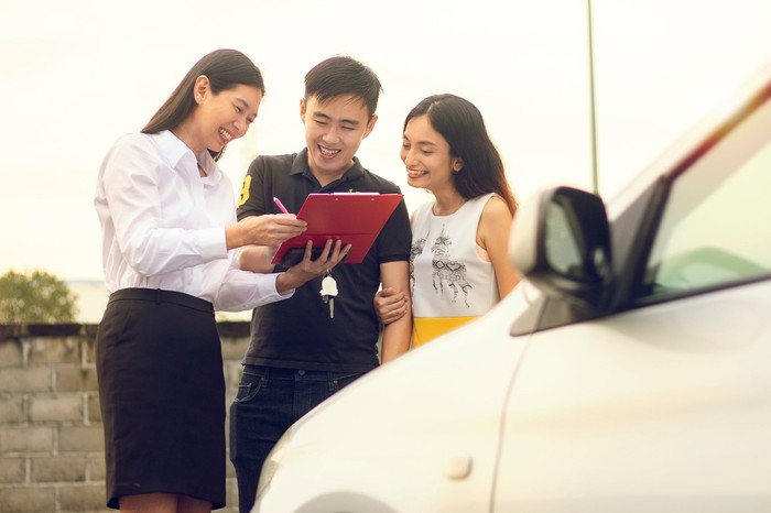An Asian couple completing the purchase of a car.