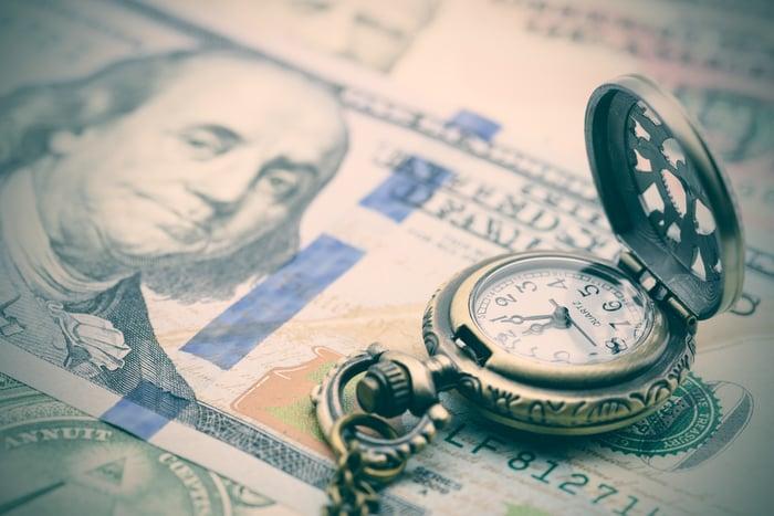 Une montre de poche antique ouverte posée sur un billet de cent dollars.