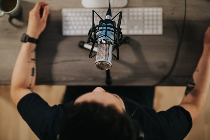 Person recording podcast on computer.