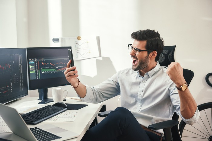 Investor excited while looking at computer screen.