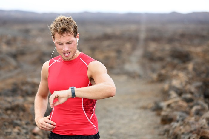 Trail runner in red tank top checking sports watch.