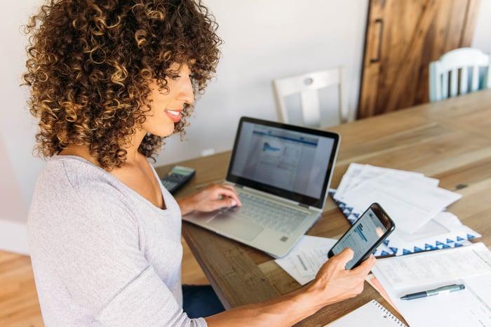Un adulte examine les finances avec un smartphone et un ordinateur portable à la maison.