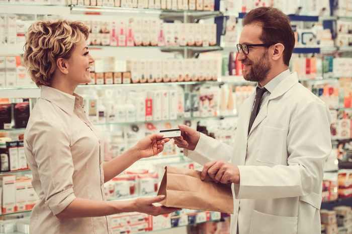 A pharmacist gives a customer their prescriptions in a drug store.