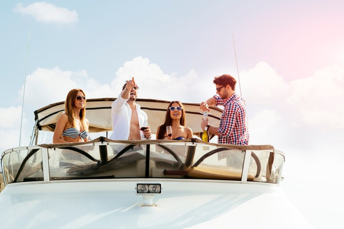 A group of young people enjoying themselves on the bow of a yacht.