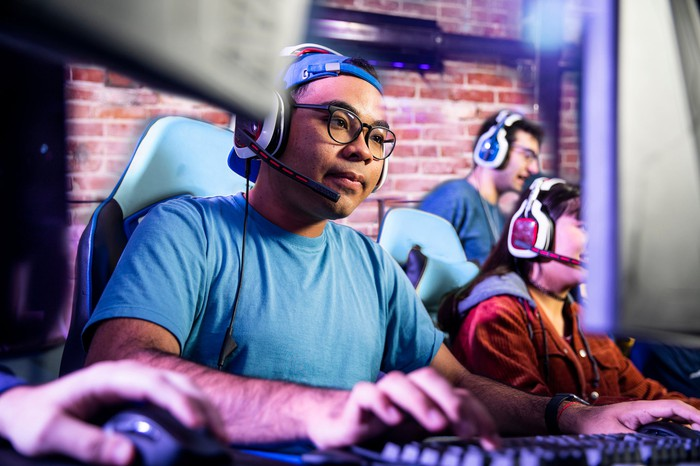 A gamer wearing headphones plays a game on a PC.