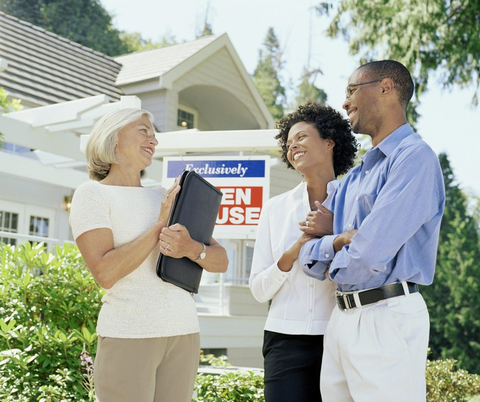 """A real estate broker and a couple stand in front of an """"Open House"""". sign."""