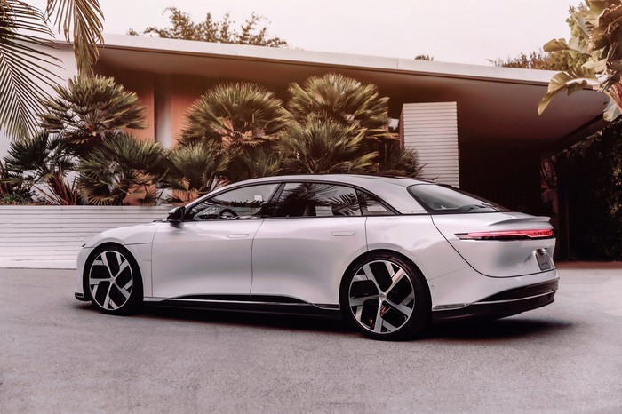 Side view of a white Lucid Air sedan parked in front of a modern home.